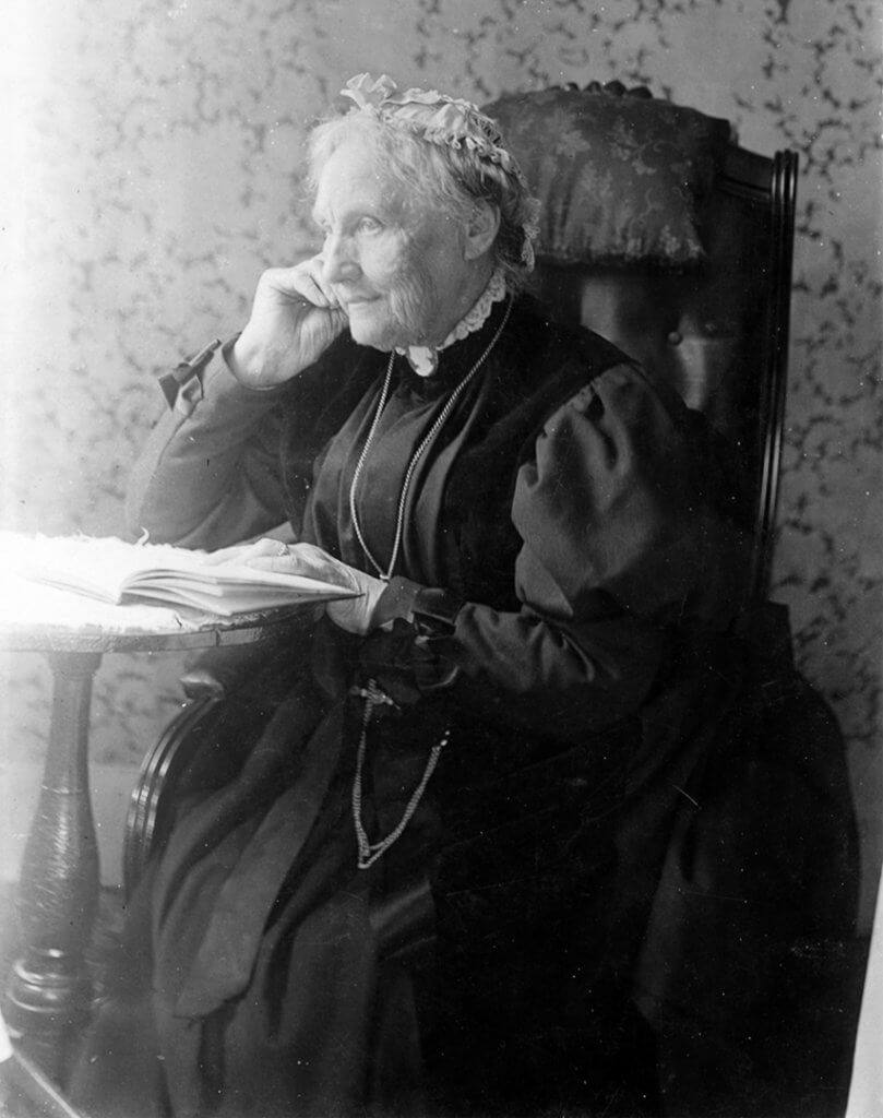 Anna Gardner, in her later years, seated at a small table reading a book.