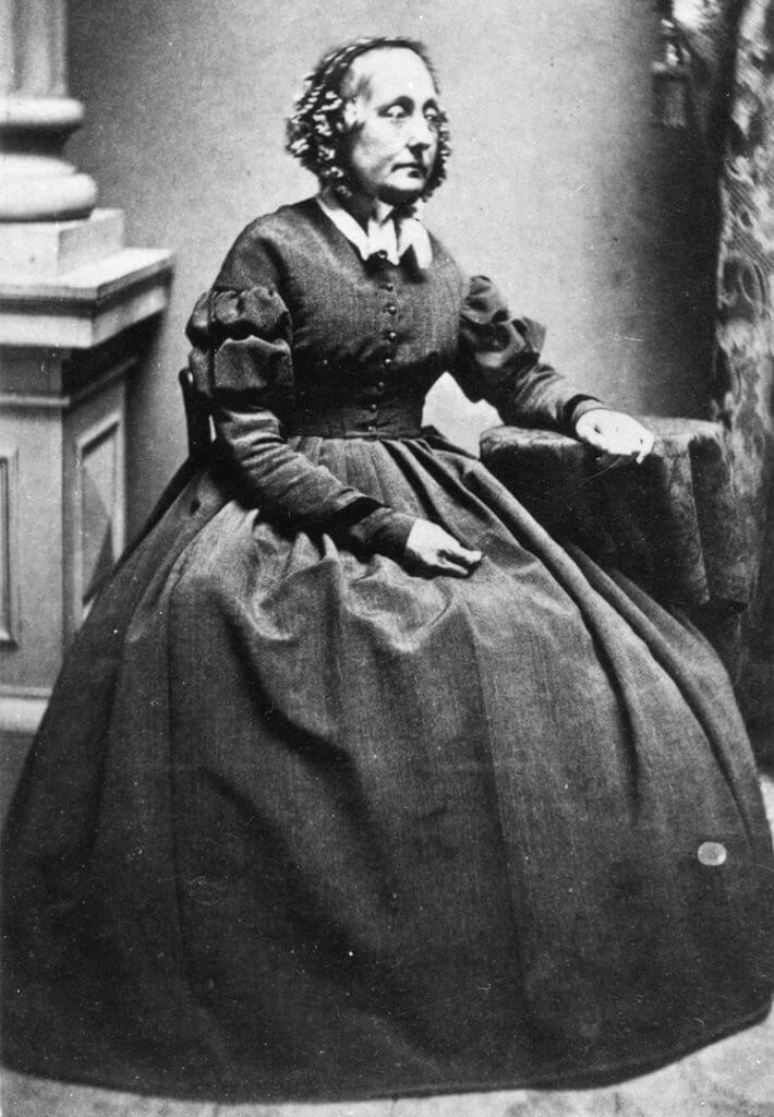 Portrait of women from mid 1800's seated in a large dress.