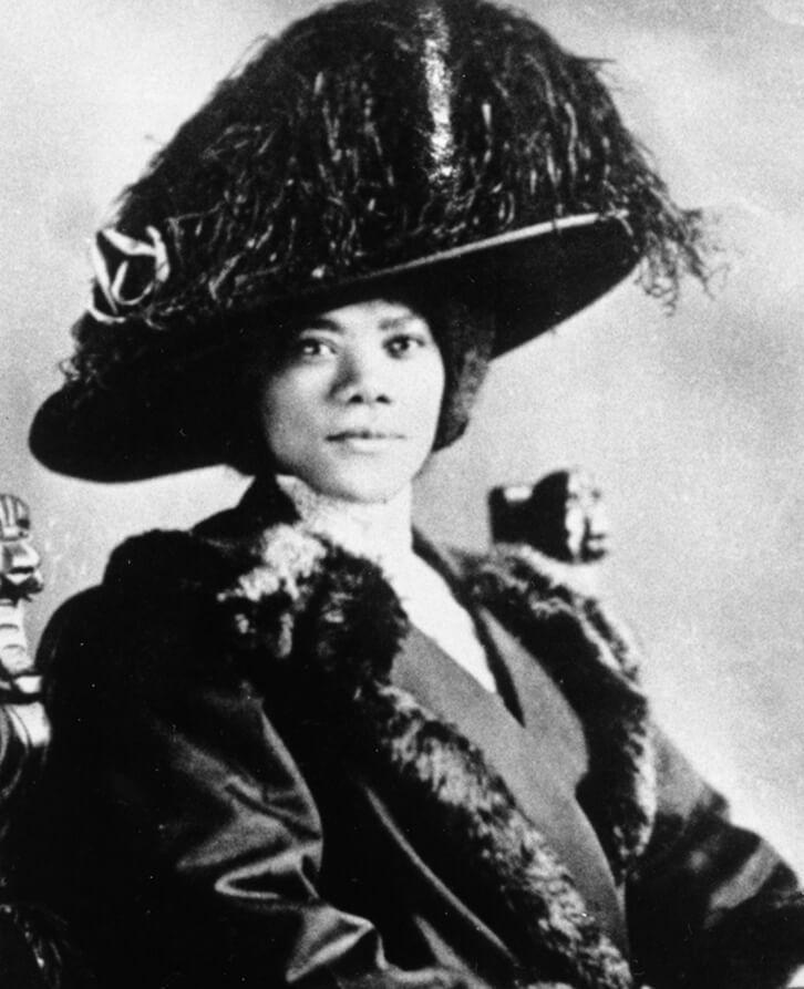 Florence Elizabeth Higginbotham, wearing a fur trimmed coat and a large feathered hat.