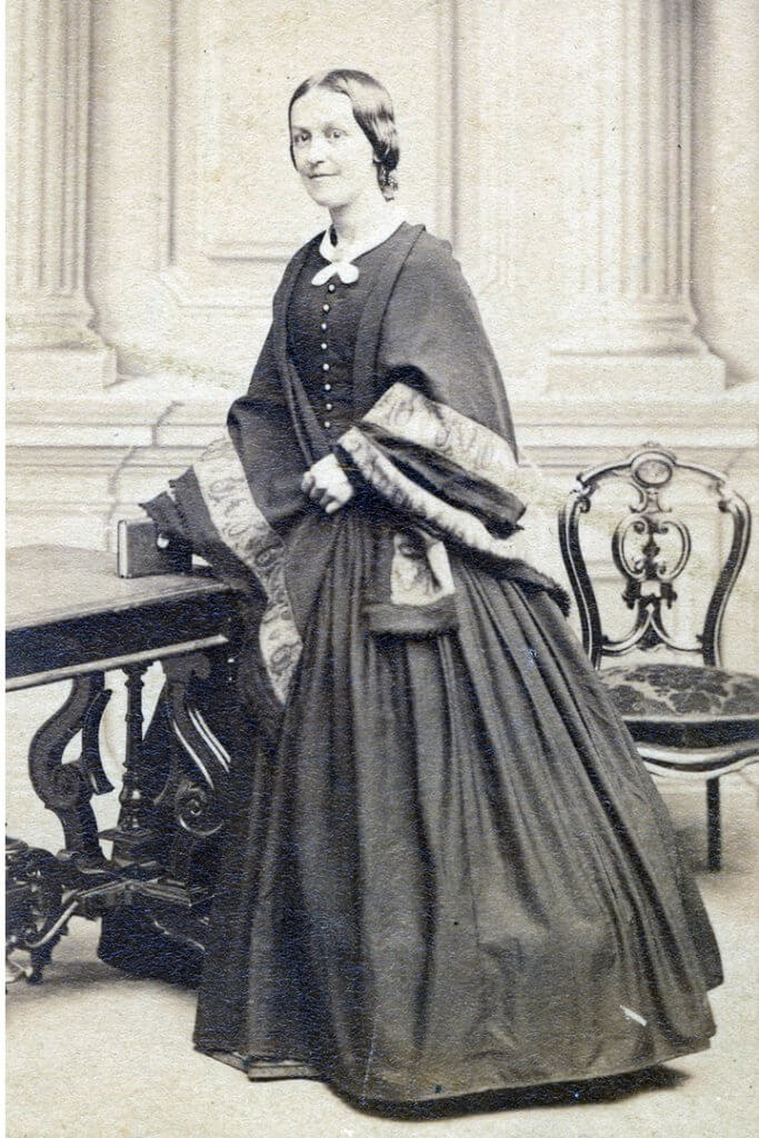 Photographic portrait of Phoebe A. Hanaford, posed standing, holding a book.